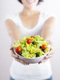Ensalada de la mujer joven y de la verdura en blanco Imagen de archivo libre de regalías