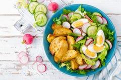 Ensalada de la patata cocida deliciosa, del huevo hervido y de las verduras frescas de la lechuga, del pepino y del rábano Menú d imagen de archivo