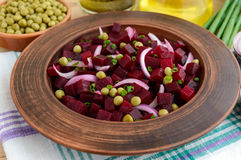 Ensalada de la vitamina de las remolachas, guisantes verdes, cebolla azul en un cuenco de la arcilla Fotografía de archivo