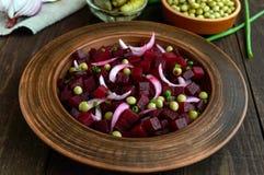 Ensalada de la vitamina de las remolachas, guisantes verdes, cebolla azul en un cuenco de la arcilla Fotografía de archivo libre de regalías