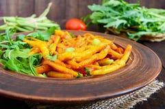 Ensalada de las habas verdes, guisadas con las cebollas en salsa de tomate y hojas verdes del arugula Foto de archivo libre de regalías