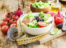Ensalada de las verduras con la cinta de la medida Concepto de la dieta sana Imagen de archivo libre de regalías