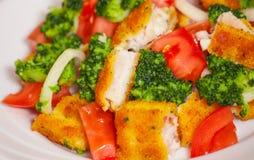 Ensalada de las verduras frescas con los prendederos de pescados empanados fritos Fotografía de archivo
