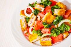 Ensalada de las verduras frescas con los prendederos de pescados empanados fritos Imagen de archivo