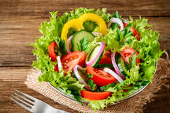Ensalada de las verduras frescas con verdes en la tabla de madera Imagen de archivo libre de regalías
