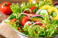 Ensalada de las verduras frescas con verdes en la tabla de madera Imagen de archivo