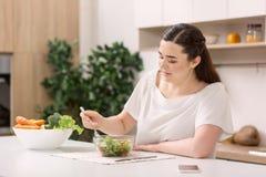 Ensalada de mezcla enfocada de la mujer atenta Foto de archivo libre de regalías