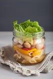 Ensalada de pasta del vegano en tarros de albañil con las aceitunas de las habas de las verduras Imagenes de archivo