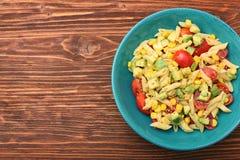 Ensalada de pasta fría con el aguacate, el tomate y el aceite de oliva Imagenes de archivo
