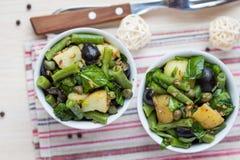 Ensalada de patata con las habas verdes, aceitunas, alcaparras, cebollas, deliciosas Imagen de archivo