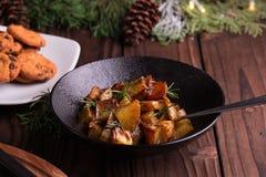Ensalada de patata dulce salteada en el cuenco negro en fondo de madera marrón Acompañamiento para la Navidad, la acción de graci Imagen de archivo libre de regalías