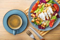 ensalada de pollo fresca con la taza de café azul Foto de archivo