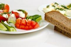 Ensalada de tomates y pepinos, huevos y pan Imagen de archivo libre de regalías