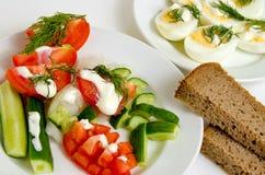 Ensalada de tomates y pepinos, huevos y pan Imagenes de archivo
