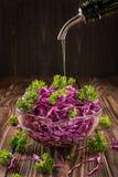 Ensalada de verduras frescas en un cuenco de ensalada en una tabla de madera asperjada con el primer del aceite de oliva Imagen de archivo