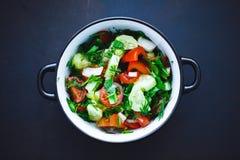 Ensalada de verduras frescas en una placa en un fondo negro, tomates, pepinos, eneldo, perejil, cebolla del verano Cierre para ar foto de archivo libre de regalías