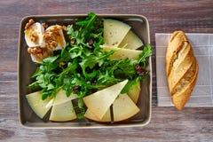 Ensalada del Arugula con la miel y las nueces del queso de cabra Imágenes de archivo libres de regalías