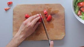 Ensalada del cocinero de las manos del cocinero en tabla de cortar de madera almacen de metraje de vídeo