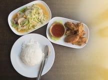 Ensalada del pepino (som Tam), alas de pollo frito, arroz cocinado, estilo tailandés de la comida fotografía de archivo