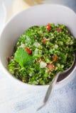 Ensalada del tabbouleh de la quinoa en una tabla de madera Foto de archivo libre de regalías