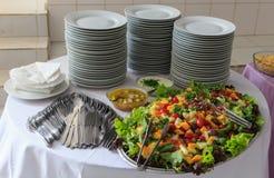 Ensalada deliciosa de verduras y de frutas Lechuga, tomate, perejil, arugula, uva, mango, melón En la tabla una pila de placas, imagen de archivo libre de regalías