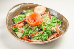Ensalada dietética del paprika, de la lechuga, del pepino, de aceitunas y del aceite de oliva, una rebanada de pan En el medio de Fotos de archivo libres de regalías