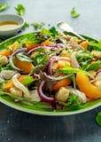Ensalada fresca con la pechuga de pollo, el melocotón, la cebolla roja, los cuscurrones y las verduras en una placa verde Aliment Imagenes de archivo