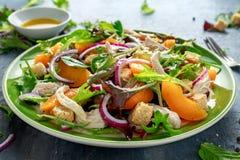 Ensalada fresca con la pechuga de pollo, el melocotón, la cebolla roja, los cuscurrones y las verduras en una placa verde Aliment Foto de archivo libre de regalías
