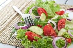 Ensalada fresca con las cebollas de los tomates de los pepinos Imagenes de archivo