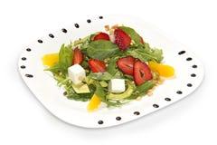 Ensalada fresca con las fresas, el arugula, las nueces de pino, el queso cremoso, el mango y el aguacate Imagenes de archivo