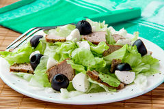 Ensalada fresca con lechuga, carne y aceitunas Fotos de archivo