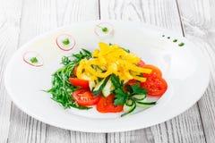 Ensalada fresca con los tomates de cereza, el pepino, el rábano, la pimienta dulce y la cebolla en una placa en cierre de madera  Foto de archivo libre de regalías