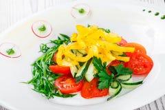 Ensalada fresca con los tomates de cereza, el pepino, el rábano, la pimienta dulce y la cebolla en una placa en cierre de madera  Imágenes de archivo libres de regalías