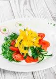 Ensalada fresca con los tomates de cereza, el pepino, el rábano, la pimienta dulce y la cebolla en una placa en fondo de madera Fotos de archivo libres de regalías