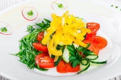 Ensalada fresca con los tomates de cereza, el pepino, el rábano, la pimienta dulce y la cebolla en una placa en fondo de madera Foto de archivo