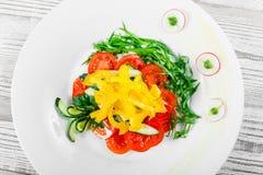 Ensalada fresca con los tomates de cereza, el pepino, el rábano, la pimienta dulce y la cebolla en una placa en fondo de madera Imágenes de archivo libres de regalías