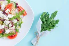 Ensalada fresca de la primavera con el pepino, el tomate, el queso y el arugula aislados en una placa blanca Fotos de archivo libres de regalías