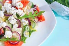 Ensalada fresca de la primavera con el pepino, el tomate, el queso y el arugula aislados en una placa blanca Foto de archivo libre de regalías