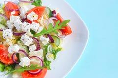 Ensalada fresca de la primavera con el pepino, el tomate, el queso y el arugula aislados en una placa blanca Fotografía de archivo libre de regalías