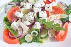 Ensalada fresca de la primavera con el pepino, el tomate, el queso y el arugula aislados en una placa blanca Imagenes de archivo