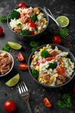 Ensalada fresca del arroz del atún con maíz dulce, los tomates de cereza, el bróculi, el perejil y la cal en cuenco negro Foto de archivo libre de regalías