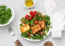 Ensalada fresca del arugula, de tomates de cereza, de los pepinos y del queso asado Imagenes de archivo
