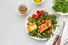 Ensalada fresca del arugula, de tomates de cereza, de los pepinos y del queso asado Fotografía de archivo