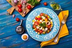 Ensalada fresca del corazón de la palma, de los tomates de cereza, del paprika amarillo, del ajo y del perejil en el fondo de mad Foto de archivo libre de regalías