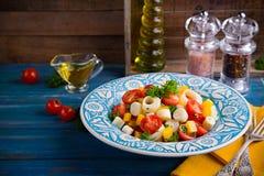 Ensalada fresca del corazón de la palma, de los tomates de cereza, del paprika amarillo, del ajo y del perejil en el fondo de mad Foto de archivo