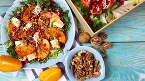 Ensalada fresca del otoño con las semillas del caqui, del arugula, del queso y de la granada Espacio para la copia imagen de archivo libre de regalías