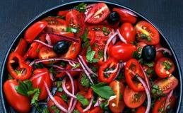 Ensalada fresca del tomate, de la cebolla, de la pimienta, de los verdes y del aceite en una placa negra, fondo negro Fotografía de archivo libre de regalías