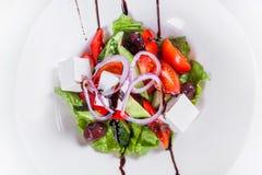Ensalada griega con las verduras frescas Plato en blanco Foto de archivo