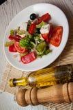 Ensalada griega con queso de cabra y aceite de oliva Imagen de archivo libre de regalías
