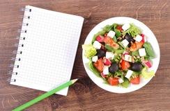 Ensalada griega fresca con las verduras y la libreta para las notas, concepto sano de la nutrición fotos de archivo libres de regalías